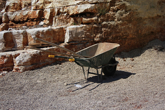 Empty construction car with tools near a stone rock
