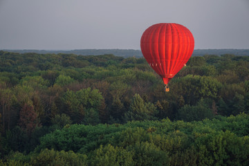 Fotobehang Ballon Red hot air balloon in the sky above the trees