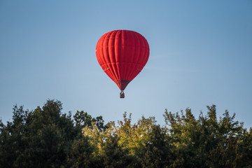 Red hot air balloon in the sky above the trees Fototapete