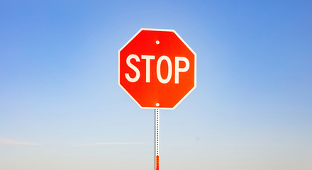 Stop sign against blue sky background. Sunny spring day