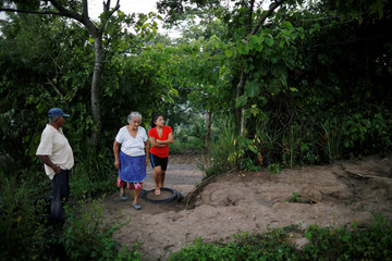 Parents Victor and Paula Gonzalez and a wife Norma Mendez of Salvadoran migrant Marvin Antonio Gonzalez, who recently died in a border detention center in New Mexico, are pictured outside their home in Verapaz
