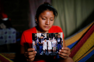 Norme Mendez, wife of Salvadoran migrant Marvin Antonio Gonzalez, who recently died in a border detention center in New Mexico, shows pictures of Marvin at her home in Verapaz