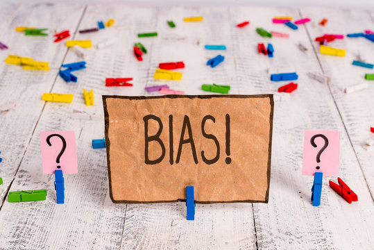 Conceptual hand writing showing Bias. Concept meaning inclination or prejudice for or against one demonstrating group Crumbling sheet with paper clips placed on the wooden table