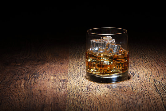 Scotch in glass tumbler with ice rocks on old wood surface