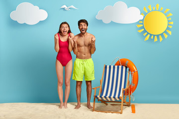 Summer holiday, vacation and tourism concept. Overjoyed happy family couple make triumphing...