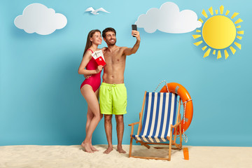 European couple takes selfie on cell phone, pose on beach with passport and flying tickets, rejoice successful traveling, focused in smartphone camera, have summer vacation, make travel photos