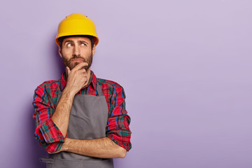Thoughtful man builder construction touches chin, thinks over new idea for building, works as repairman, wears yellow protective helmet, checkered shirt and apron. Industry and repairing concept