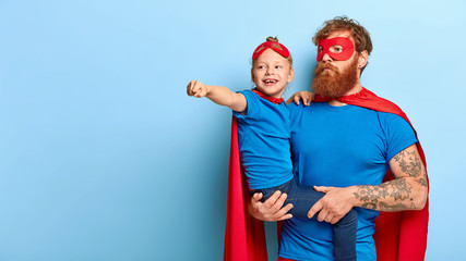 Father and little female child ready for New Year carnival, wear superhero suits, girl keeps arm outstretched, clenches fist, pretends flying and protect people, isolated on blue background.