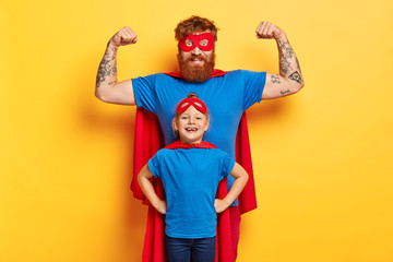 Family fun concept. Joyful strong father raises arms and shows biceps, ready to defend his daughter, stands back, imagine they are superheroes, wears costumes, isolated on yellow background.