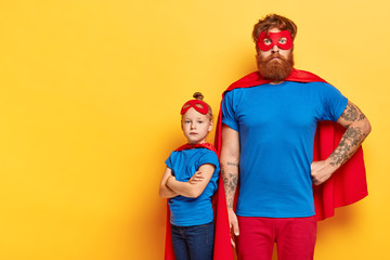 Photo of serious bearded man and self confident little child stands near with crossed arms, wears superhero costumes, show courage, put their life to risk, posses brave deeds and noble qualities