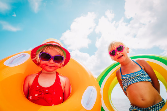 happy cute little girls with floaties at tropical beach