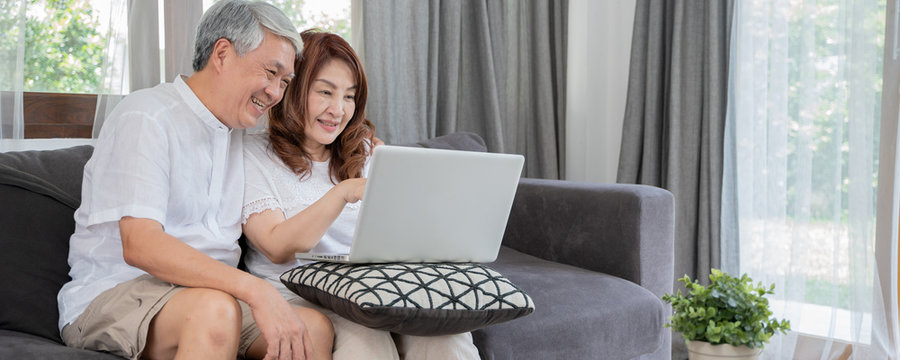 Happy Asian Senior Couple  lifestyle technology device concept,Lovely elderly couple using laptop computer on bed.Banner background with copy space