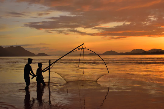 People fishing in river brahmaputra during sunset.