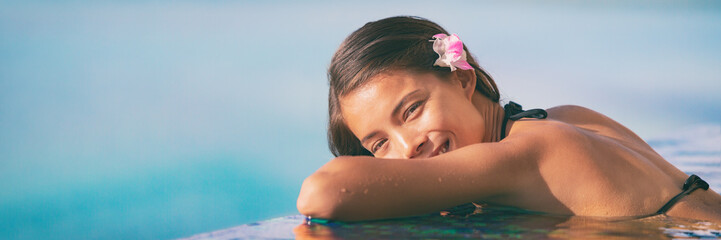 Wall Mural - Spa wellness woman relaxing in blue panoramic banner. Happy Asian woman at luxury hotel resort overwater infinity pool.