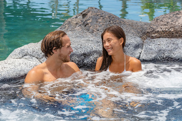 Wall Mural - Spa jacuzzi hot tub pool couple happy relaxing on resort holiday hotel honeymoon wellness retreat. luxury vacation on tropical destination. Asian woman laughing talking to caucasian man.