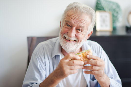 Seniors European man is sitting to eat a burger at home which looking at camera. Retired man is smiling with felling happy and take a burger on hand.