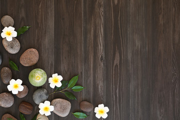 Flat lay composition with spa stones, flowers and candle on wooden background. Space for text