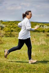 Spanish woman running on meadow