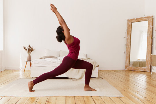 Attractive flexible young dark-skinned female in sportswear training indoors, doing yoga, standing on floor in warrior 1 pose, feet wide apart, raising hands above her head, breathing deeply