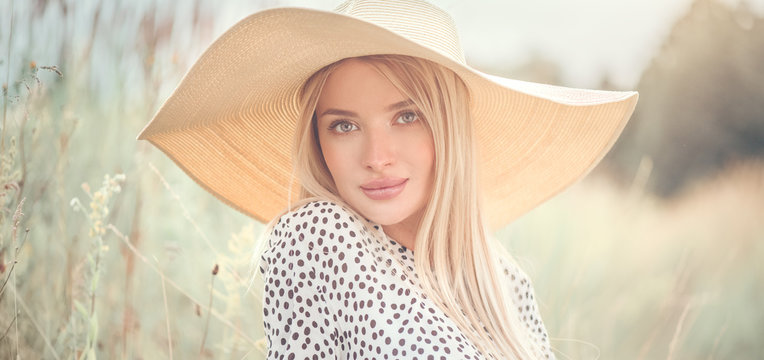Beautiful model girl posing on a field, enjoying nature outdoors in wide brimmed straw hat. Beauty blonde young woman with long straight blond hair closeup portrait
