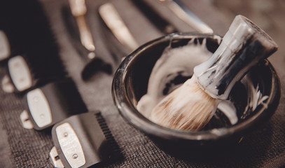 Brush for applying foam on beard man shaving with razor in barbershop background of tools