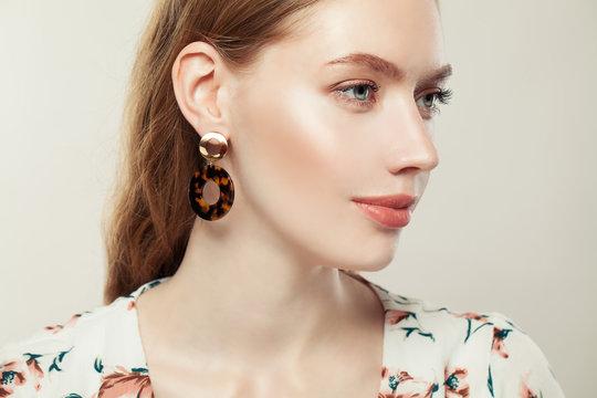 Jewelry woman wearing fashion golden earrings on white background, elegant female profile