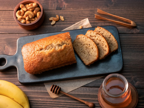 Homemade banana bread pound sliced with cashew nuts and honey on wooden table.