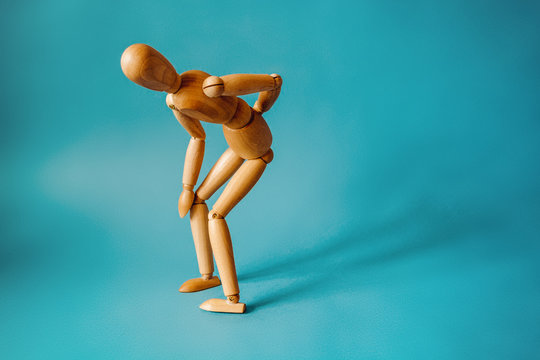 Concept of back pain. A wooden figure depicts a pain in the back.