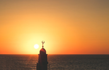 minaret tower with Islamic crescent religion sign architecture silhouette on atmospheric sunset above Mediterranean sea scenic landscape idyllic background with empty space for copy or text Wall mural