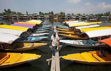 A boatman walks past the parked 'Shikaras' or boats for tourists on the banks of Dal Lake in Srinagar