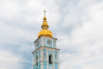The bell tower of Saint Michael's Golden-Domed Monastery on the background of gray sky with clouds.