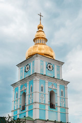 The bell tower of Saint Michael's Golden-Domed Monastery on the background of gray sky with clouds, vertical image.