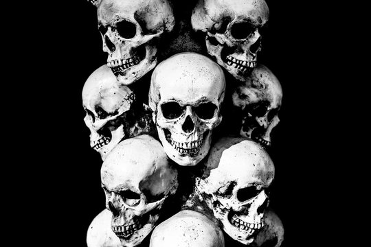 Gloomy skulls on a dark background. Skulls stand on top of each other.