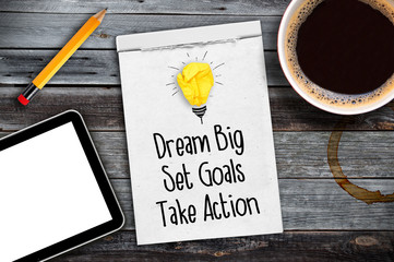 Sketchbook with Dream big, set goals, take action on a wooden desk with coffee, pen and tablet