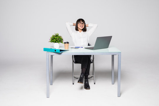 Business woman relaxing with her hands behind her head and sitting on chair