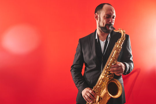 Portrait of professional musician saxophonist man in  suit plays jazz music on saxophone, red background in a photo studio