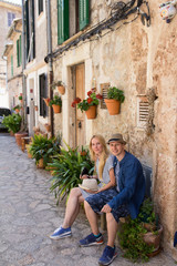 young couple sitting on bench on romantic mediterranean street