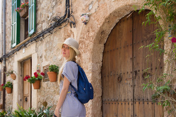 woman tourist wearing summer hat posing on street in mediterranean town in summer season