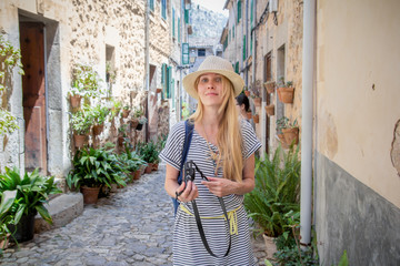 young woman tourist with camera walking down the charming street in mediterranean town in summer