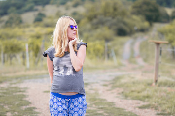 young pregnant woman posing in nature
