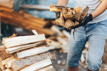A pile of stacked firewood, prepared for heating the house. Gathering fire wood for winter or bonfire. Man holds fire wood in hands