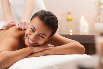 Portrait of beautiful young woman smiling at camera while enjoying massage in spa, copy space