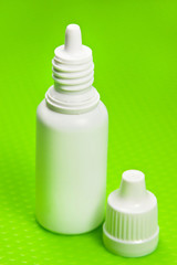 Medical eye drops and green background