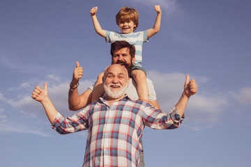 Father son and grandfather playing - family time together. Boy with father and grandfather. Male multi generation portrait. Three men generation.