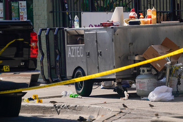 Evidence markers lay on the ground near a hotdog stand after a mass shooting in Dayton