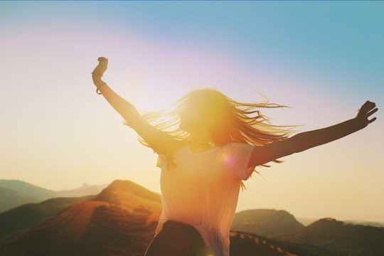 Girl on a background of mountains joyful spread her arms dancing at a height 2