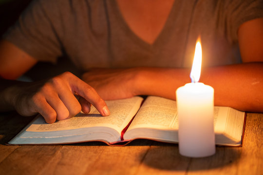 close up of Christian boys  are reading and study bible In the room and lit candles to light, Religious concepts