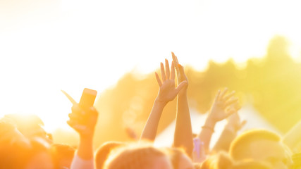 People raised their hands and dance in the open air concert in the setting sun