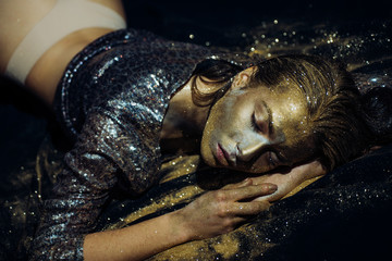 Vogue and glamour concept. Golden skin. Sexy girl face makeup body art metallized color. Spa wellness. Richness and wellbeing. Luxury beauty procedure. Golden mask. Golden lady relaxing. Pure gold