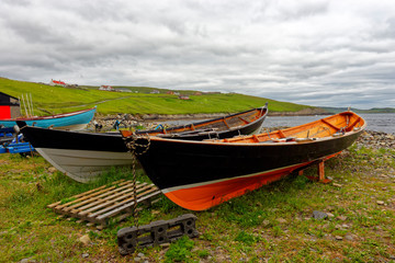 Old wooden boats stored on shore at Sandwick on the Main Shetland Isle, which is located northeast of the Scottish mainland